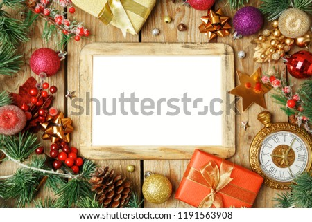 Christmas holiday background with photo frame, decorations and ornaments on wooden table. Top view from above.
