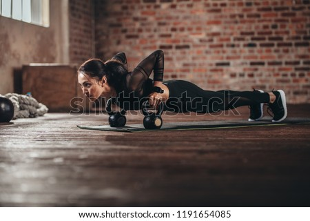 Fit female doing intense core workout in gym. Young woman doing push up exercise on fitness mat in health club. #1191654085