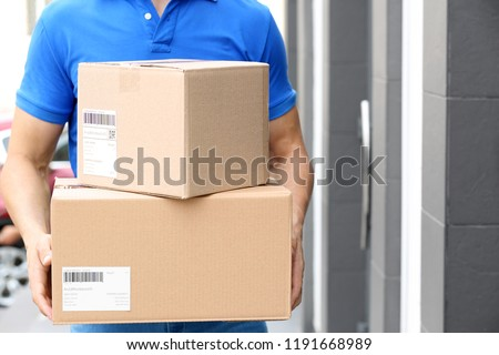 Delivery service courier with parcels in hands outdoors #1191668989