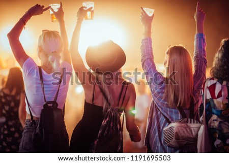 Back view of group of female friends at music festival drinking beer and dancing #1191695503