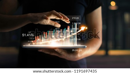 Businessman holding tablet and showing a growing virtual hologram of statistics, graph and chart with arrow up on dark background. Stock market. Business growth, planing and strategy concept.  Royalty-Free Stock Photo #1191697435