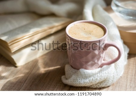 A Cup of hot cappuccino coffee with old book and warm scarf a on wooden table. Autumn mood concept. Winter mood concept. Warm autumn or winter picture. Selective focus. At home. Time for relax.