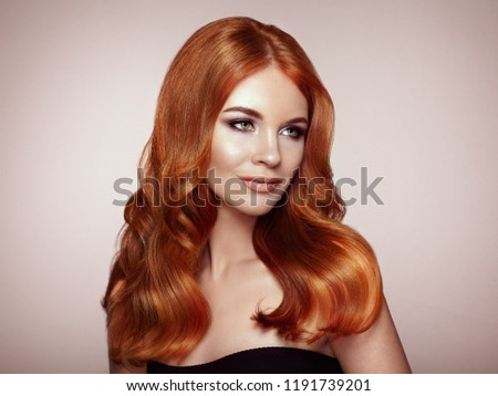 Redhead Girl with Long Healthy and Shiny Curly Hair. Care and Beauty. Beautiful Model Woman with Wavy Hairstyle. Make-Up and Black Dress #1191739201