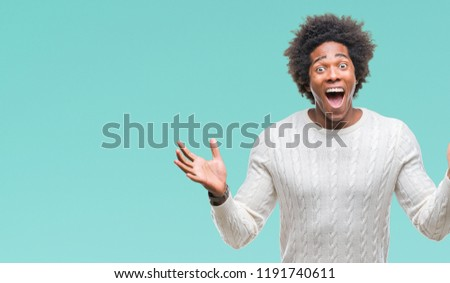 Afro american man over isolated background celebrating crazy and amazed for success with arms raised and open eyes screaming excited. Winner concept #1191740611