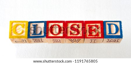 The term closed visually displayed in wooden toy blocks on a white background image with copy space in landscape format