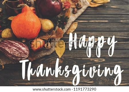 Happy Thanksgiving Text on Pumpkin, autumn vegetables with colorful leaves,acorns,nuts, berries on wooden rustic table, flat lay. Seasons greeting card. Atmospheric image