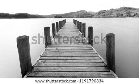 A Jetty stretching out over a lake shot in black and white. #1191790834