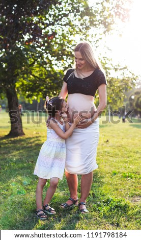Cute little girl hugging and kissing her mother's pregnant belly in summer nature