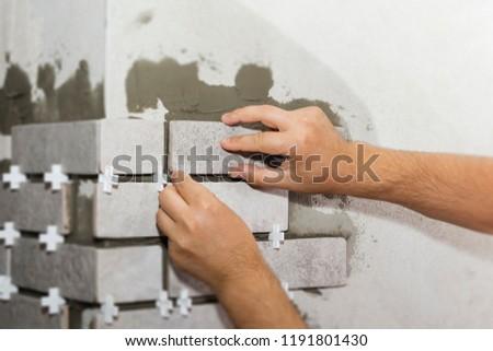 Laying Ceramic Tiles. The Builder makes repairs. #1191801430