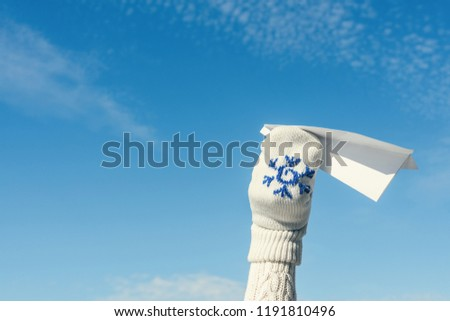 A girl in the winter knitted mittens is launching a paper airplane on the blue sky background. Christmas and New Year concept #1191810496