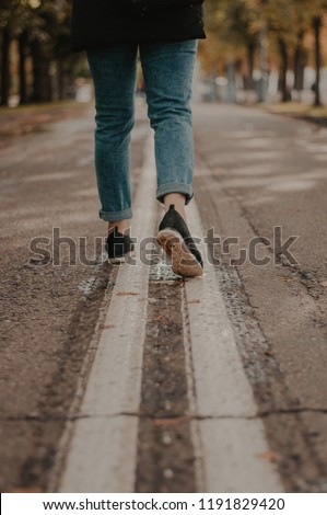 Woman running in the street. Feet closeup in the autumn park #1191829420