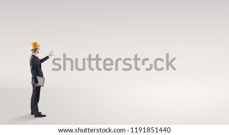 Young architect with construction helmet standing in an empty space and holding a plan #1191851440