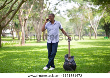 Smiling black guitarist talking on mobile phone in park. Handsome black man standing and holding guitar. Guitarist and communication concept. Front view with grass and trees in background. #1191861472