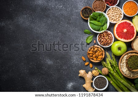 Superfoods on black stone background. Legumes, nuts, chia, avocado, grapefruit, beans, goji, green apple and asparagus and quinoa. Top view copy space. #1191878434