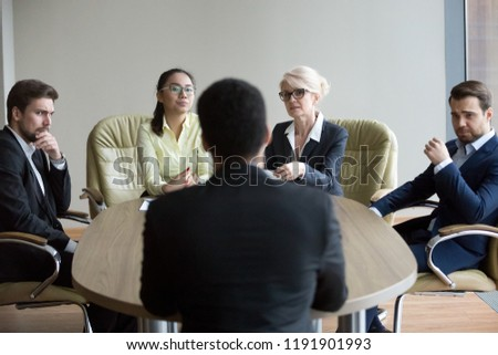 Doubtful recruiting managers look at African American applicant, unsure about candidature for open position, concerned dissatisfied employers consider black candidate at hiring. Discrimination concept Royalty-Free Stock Photo #1191901993