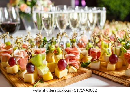 the buffet at the reception. Glasses of wine and champagne. Assortment of canapes on wooden board. Banquet service. catering food, snacks with cheese, jamon, prosciutto and fruit #1191948082