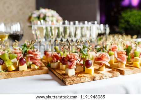 the buffet at the reception. Glasses of wine and champagne. Assortment of canapes on wooden board. Banquet service. catering food, snacks with cheese, jamon, prosciutto and fruit #1191948085