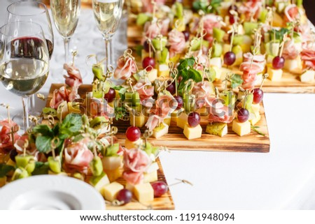 Light snacks in a plate on a buffet table. Assorted mini canapes, delicacies and snacks, restaurant food at event. A gala reception. Decorated delicious table for a party goodies. #1191948094