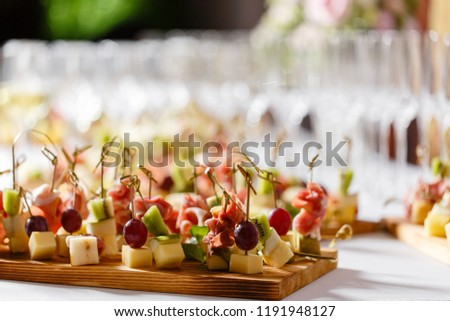 the buffet at the reception. Glasses of wine and champagne. Assortment of canapes on wooden board. Banquet service. catering food, snacks with cheese, jamon, prosciutto and fruit #1191948127