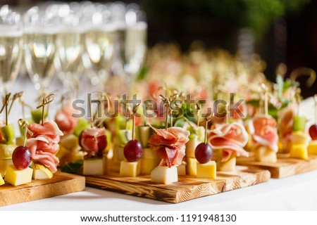 the buffet at the reception. Glasses of wine and champagne. Assortment of canapes on wooden board. Banquet service. catering food, snacks with cheese, jamon, prosciutto and fruit #1191948130