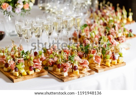 the buffet at the reception. Glasses of wine and champagne. Assortment of canapes on wooden board. Banquet service. catering food, snacks with cheese, jamon, prosciutto and fruit #1191948136