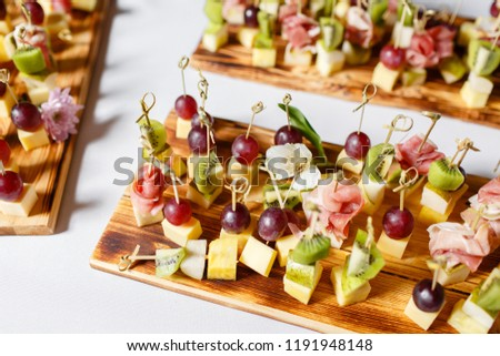 Light snacks in a plate on a buffet table. Assorted mini canapes, delicacies and snacks, restaurant food at event. A gala reception. Decorated delicious table for a party goodies. #1191948148