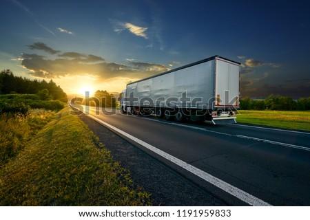 Truck driving on the asphalt road in rural landscape at sunset                                #1191959833