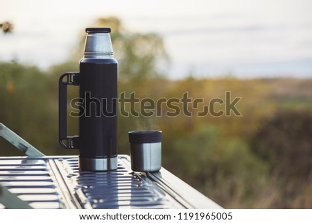 Thermos and cup with warm tea on the pick-up trunk #1191965005