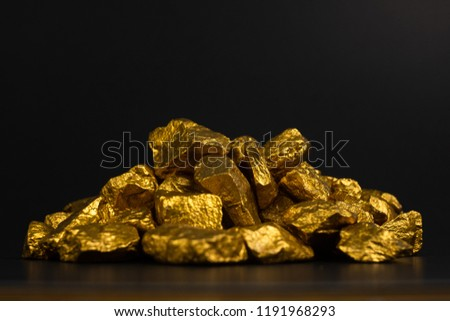 A pile of gold nuggets or gold ore on black background, precious stone or lump of golden stone, financial and business concept idea. #1191968293
