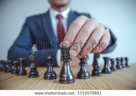 Retro style image of a businessman with clasped hands planning strategy with chess figures on an old wooden table. #1192070881