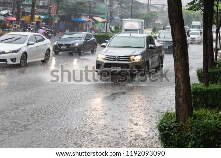 BANGKOK, THAILAND - SEPTEMBER 20, 2018 : Flooding in Bangna, Bangkok. effect of heavy raining on the road. car splashes through a large puddle on flooded street ,traffic jam in Bangkok, Thailand.  #1192093090