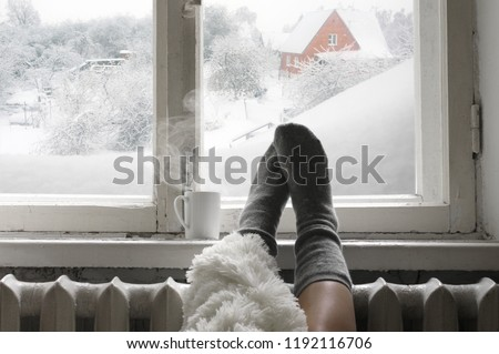 Cozy winter still life: woman legs in warm woolen socks under shaggy blanket and mug of hot beverage on old windowsill against snow landscape from outside. #1192116706