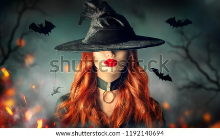Halloween Sexy Witch girl portrait. Beautiful young woman in witches hat with long curly red hair and bright lips makeup. Over spooky dark magic forest background. Wide Halloween party art design #1192140694