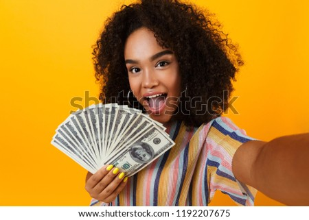 Picture of excited young african woman posing isolated over yellow background holding money make selfie by camera.