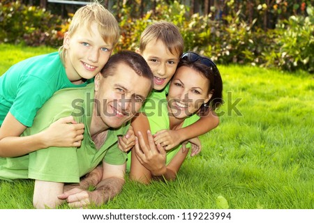 happy parents and children lie on the green grass #119223994