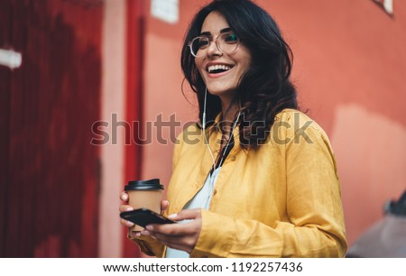 Happy girl in hipster eyeglasses listening to music while going to work, cheerful hispanic woman drinking coffee outdoors using modern smartphone device, happy smiling european businesswoman walking #1192257436