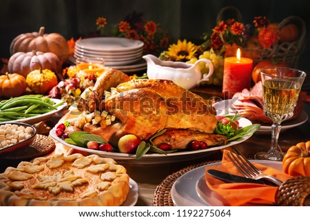 Thanksgiving dinner. Roasted turkey garnished with cranberries on a rustic style table decoraded with pumpkins, vegetables, pie, flowers and candles #1192275064