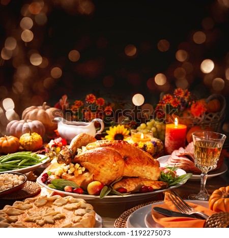 Thanksgiving dinner. Roasted turkey garnished with cranberries on a rustic style table decoraded with pumpkins, vegetables, pie, flowers and candles #1192275073