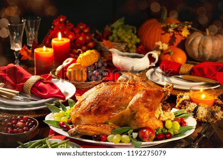 Thanksgiving dinner. Roasted turkey garnished with cranberries on a rustic style table decoraded with pumpkins, vegetables, pie, flowers and candles #1192275079
