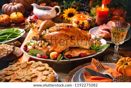 Thanksgiving dinner. Roasted turkey garnished with cranberries on a rustic style table decoraded with pumpkins, vegetables, pie, flowers and candles #1192275082