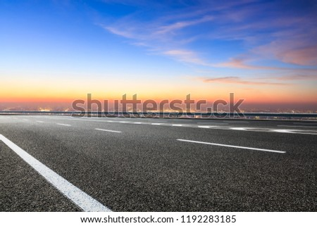 Modern city skyline and buildings with empty asphalt road at sunset #1192283185