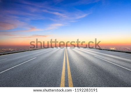 Modern city skyline and buildings with empty asphalt road at sunset #1192283191