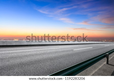 Modern city skyline and buildings with empty asphalt road at sunset #1192283206
