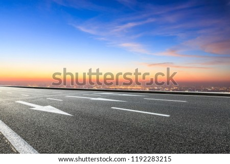 Modern city skyline and buildings with empty asphalt road at sunset #1192283215