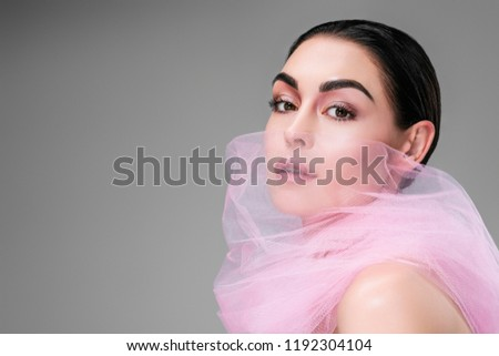 beautiful young woman with pink veil on face looking at camera isolated on grey  #1192304104