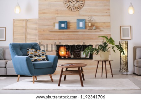 Cozy furnished apartment with niche in wooden wall and armchair. Interior design #1192341706