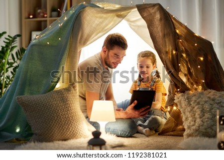 family, hygge and technology concept - happy father and little daughter with tablet pc computer in kids tent at night at home #1192381021