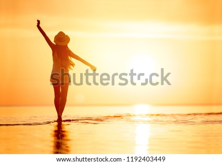 Lady's silhouette with raised arms against calm sunset beach #1192403449