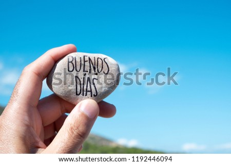 closeup of a young caucasian man showing a stone with the text buenos dias, good morning in spanish written in it, holding it against the blue sky #1192446094