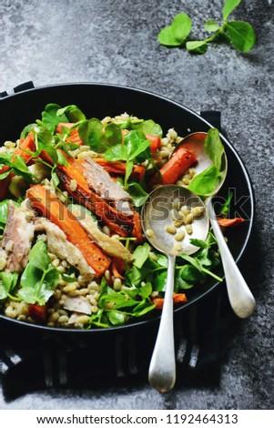 Roasted carrot, barley and smoked mackerel salad isolated on black background  #1192464313